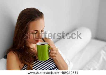 Beautiful Happy Young Woman Drinking Cup Of Coffee In Morning. Closeup Portrait Of Smiling Girl Enjoying Her Drink While Lying In Bed After Waking Up, Relaxing At Home.