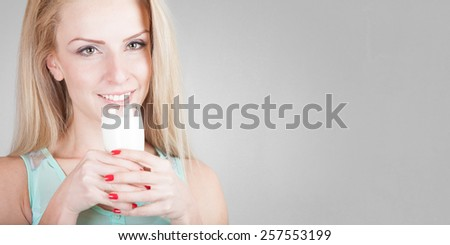 Beautiful happy young woman drinking milk - isolated on old grey wall background with place for your text - stock photo