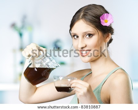 beautiful happy young woman drinking tea in the kitchen - stock photo