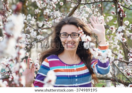 Beautiful happy young woman enjoying smell in a flowering spring garden. - stock photo
