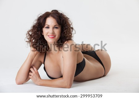Beautiful happy young woman in black lingerie in studio  - stock photo