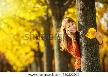 Beautiful happy young woman in the autumn park. Joyful woman is talking on a smart phone outdoors in a bright yellow trees in fall. Colourful fall concept. - stock photo