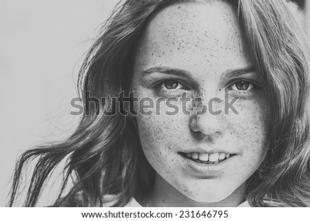 beautiful  happy young woman portrait face  with freckles and smile  black and white - stock photo