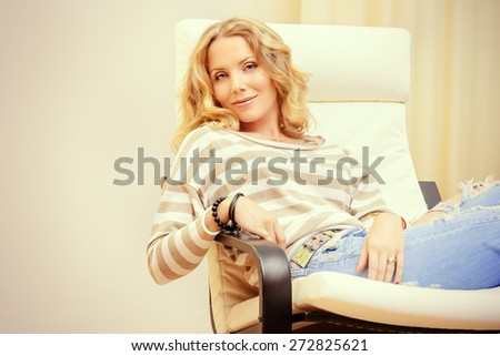 Beautiful happy young woman resting at home in a cozy armchair. Interior. - stock photo