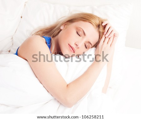 beautiful happy young woman sleeping in bed at home - stock photo