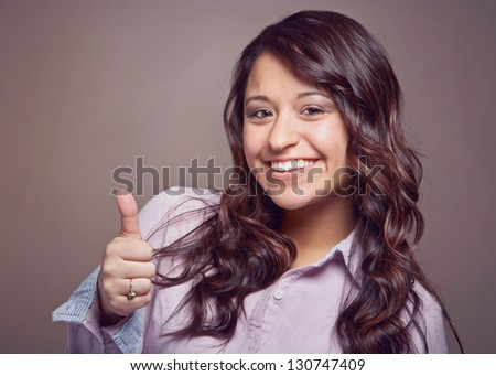 Beautiful happy young woman thumbs up