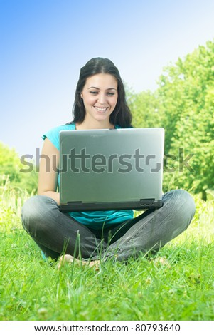 Beautiful happy young woman using laptop outdoors.