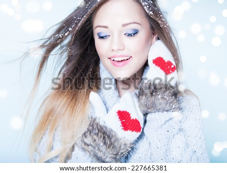 Beautiful happy young woman wearing winter gloves covered with snow flakes. Christmas portrait concept. - stock photo