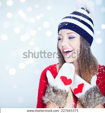 Beautiful happy young woman wearing winter hat and gloves covered with snow flakes. Christmas portrait concept. - stock photo