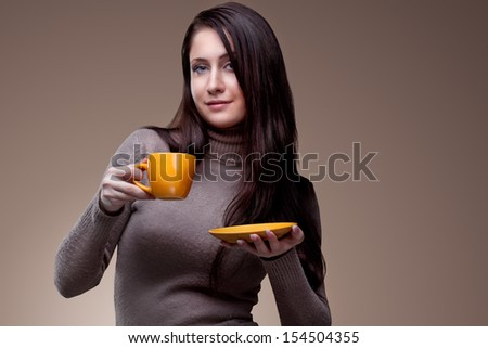 Beautiful happy young woman  with cup of aromatic coffee or tea on natural background