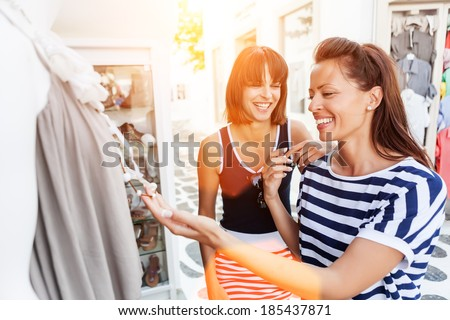 Beautiful, happy young women walking through the streets of Mykonos , looking and choosing clothes, jewelery,gifts in the street markets.Flare light - stock photo