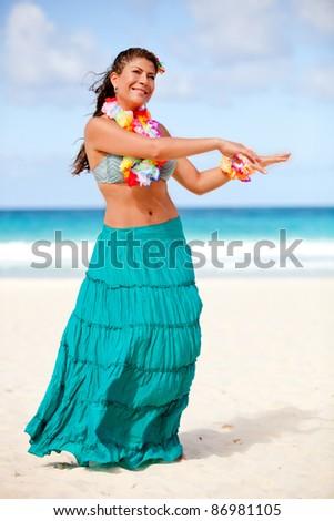 Beautiful Hawaiian woman dancing hula at the beach - stock photo
