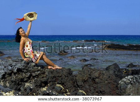 Beautiful hawaiian woman sits on a rocky beach of the Kohala Coast and waves a welcome.  She is wearing a sundress and waving a straw hat with colorful scarf. - stock photo
