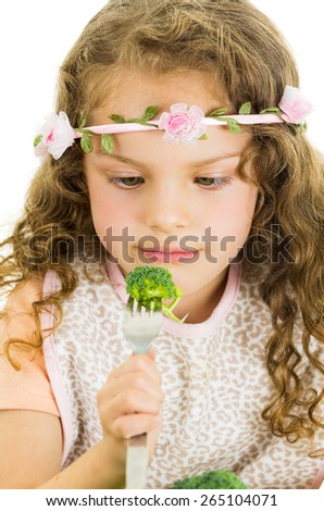 Beautiful healthy little curly girl enjoying eating broccoli isolated on white - stock photo