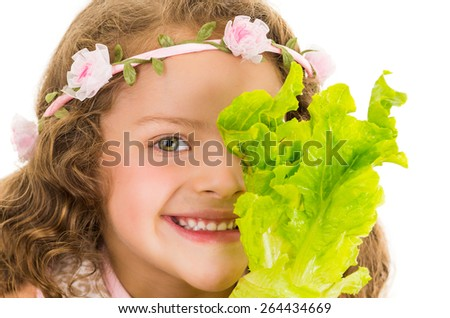 Beautiful healthy little curly girl enjoying holding lettuce in front of her eye a isolated on white - stock photo
