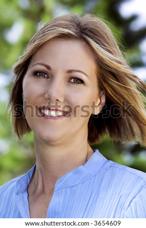 Beautiful healthy middle-aged woman in a blue blouse - stock photo