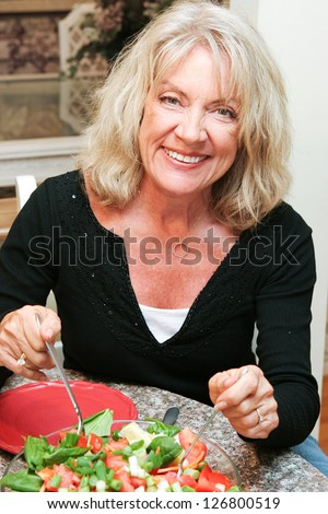 Beautiful healthy middle aged woman sitting down to eat a healthy green salad. - stock photo
