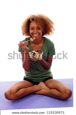 Beautiful healthy mixed Black Hispanic / Latin woman eating a fresh healthy salad, sitting on the mat isolated over white background - stock photo