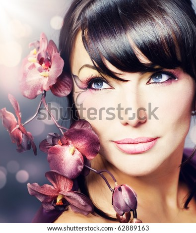 Beautiful Healthy Woman with Orchid flower - stock photo