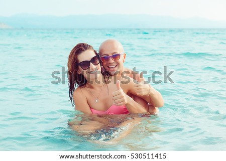 Beautiful healthy young people having fun in sea outdoors background. Multiracial couple in water travel vacation Sardinia destination. Happy smiling man and woman showing like finger hands gesture.