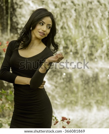 Beautiful healthy young woman in calm serene outdoor location, waterfall in background. - stock photo