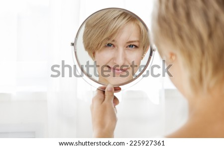 Beautiful healthy young woman looking in the mirror in the morning - stock photo