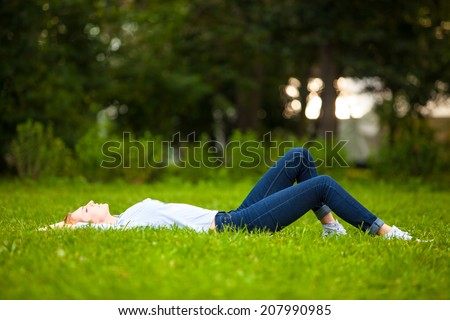 Beautiful healthy Young Woman lying and relaxing on the green grass - stock photo