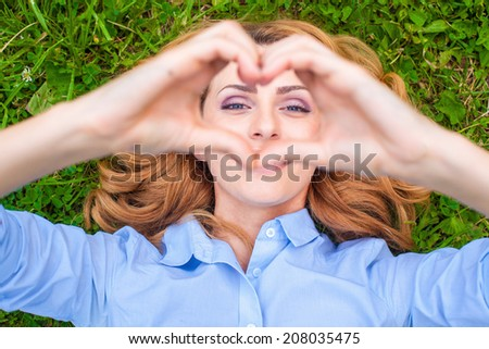 Beautiful healthy Young Woman lying and relaxing on the green grass, showing heart sign - stock photo