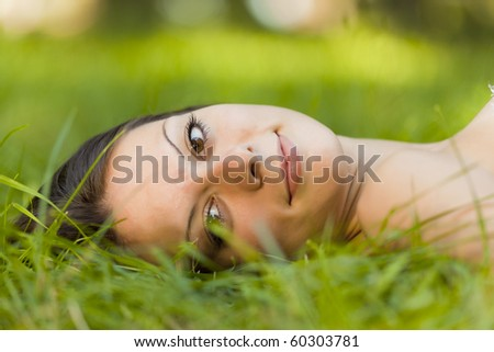 Beautiful healthy young woman lying on the green grass - stock photo