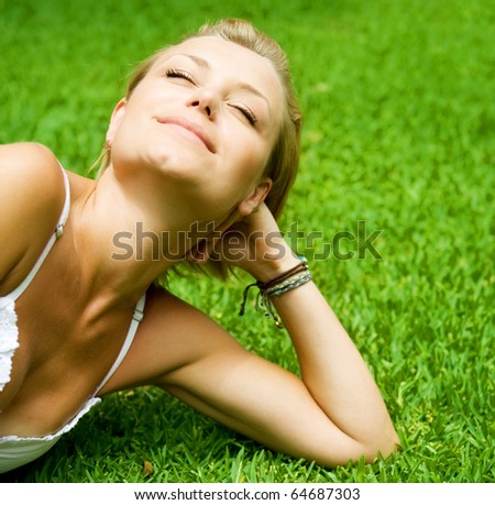 Beautiful healthy Young Woman relaxing on the green grass - stock photo