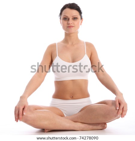 Beautiful healthy young woman wearing white sports underwear, sitting cross legged on floor against white background showing off fit body. - stock photo