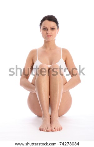 Beautiful healthy young woman wearing white sports underwear, sitting on floor with knees raised against white background showing off fit body. - stock photo