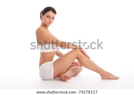 Beautiful healthy young woman wearing white sports underwear, sitting on floor with one knee raised against white background showing off fit body and long legs. - stock photo