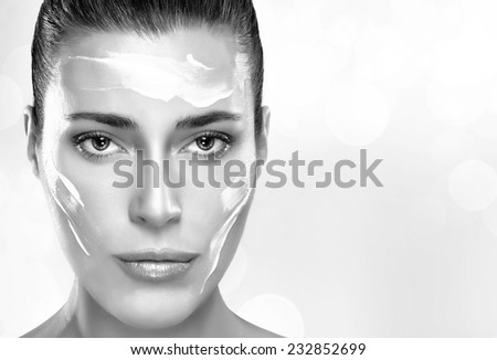 Beautiful healthy young woman with moisturizer in her clean face, close-up portrait in black and white. Skin care concept. Spa Treatment - stock photo
