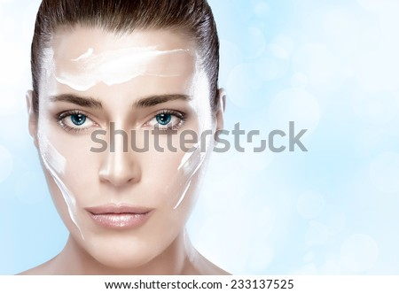 Beautiful healthy young woman with moisturizer in her clean face, close-up portrait. Skin care concept. Spa Treatment - stock photo