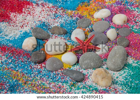 Beautiful heart background on colored sand made from seashells of different shapes and stones - stock photo