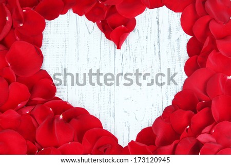 Beautiful heart of red rose petals on wooden table close-up - stock photo