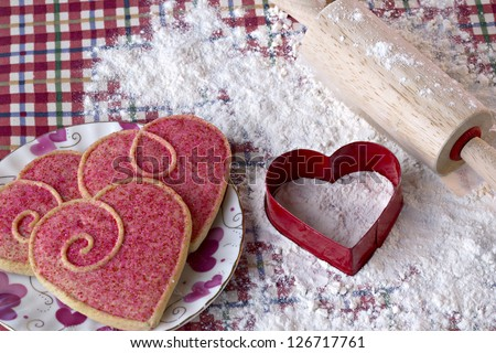 Beautiful heart shaped cookies, cutter and rolling pin in flour on red checked cloth - stock photo