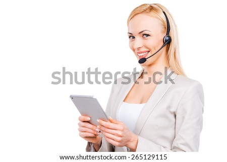 Beautiful helper. Confident mature customer service representative working on digital tablet and smiling while standing against white background - stock photo