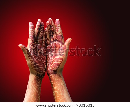 Beautiful henna or mehendi decoration on a hindu bride's hand with hand in praying style. - stock photo