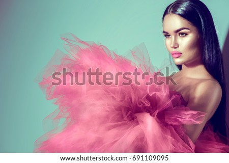 Beautiful High fashion woman in violet color dress posing in studio. Gorgeous brunette model girl with beautiful hairstyle and make-up, Wearing Stunning evening red dress with long gown of tulle