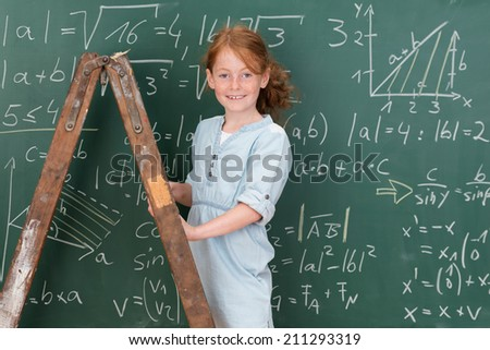 Beautiful highly intelligent little girl standing on a stepladder in the classroom to reach the mathematical equations on the board giving the camera a lovely smile - stock photo