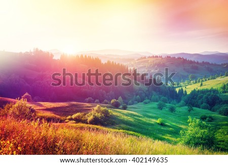 Beautiful hills glowing by sunlight at twilight. Dramatic scene. Colorful sky. Carpathian, Ukraine, Europe. Beauty world. Cross processed retro and vintage style. Instagram toning effect. Soft filter. - stock photo