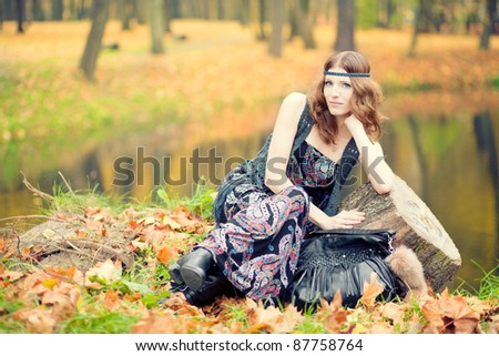 Beautiful hippie girl by the lake in autumn scenery wearing maxi long dress and gorgeous make up. - stock photo