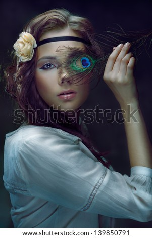 Beautiful hippie girl covering one eye with a peacock feather on dark background, toned image - stock photo