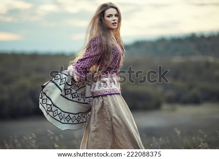 Beautiful hippie girl jumping outdoors at sunset. Boho fashion style - stock photo