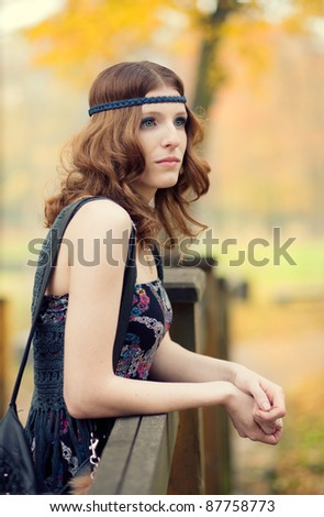 Beautiful hippie girl thinking on a wooden bridge in autumn scenery wearing maxi long dress and gorgeous make up. - stock photo