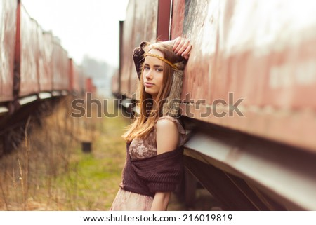 beautiful hippie girl with red hair and big lips stands near the old car near the railroad - stock photo