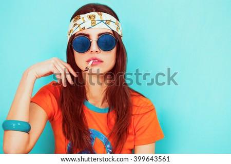 Beautiful hippy girl portrait smoking and wearing sunglasses - stock photo