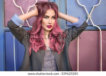 Beautiful hipster fashion model with curly pink hair posing in front of the colorful wall - stock photo